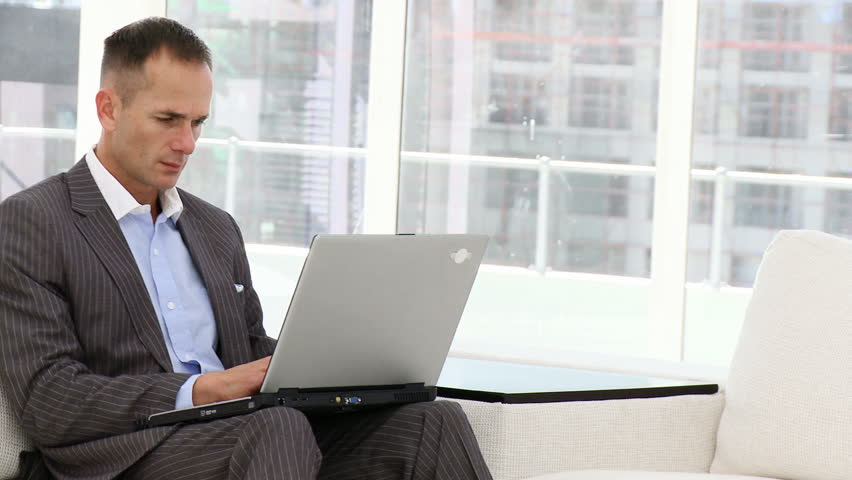 Handsome business man working at a laptop sitting on sofa - HD stock video clip