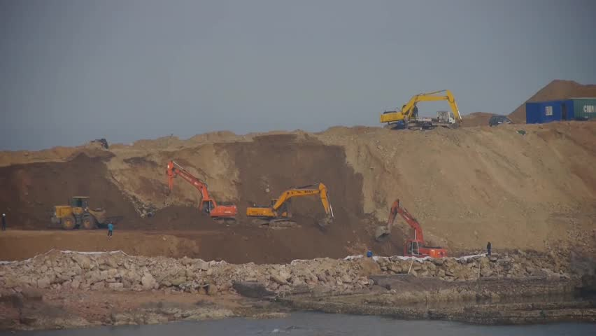 Excavator working & dumper truck on construction site near sea. gh2_06105