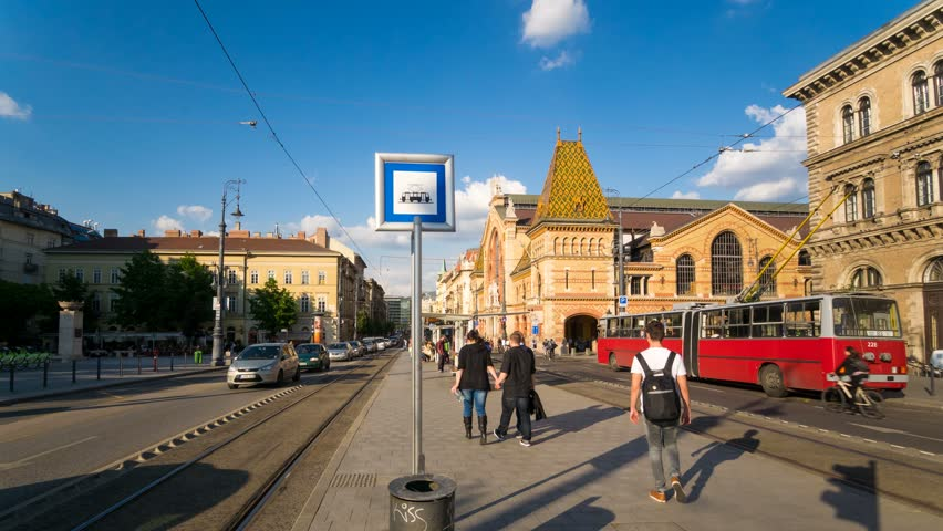 BUDAPEST - 28 MAY: Timelapse view of a tram stop outside the Great Market Hall  in central Budapest on a clear day on 28 May 2014 in Budapest, Hungary