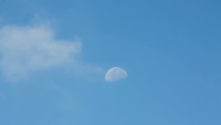 The moon in daytime with clouds moving.