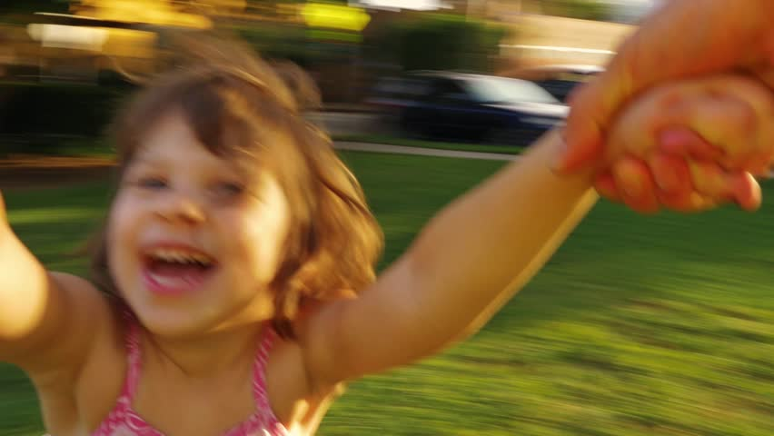 POV video of father spinning happy girl daughter child around in park at sunset. Slow motion.