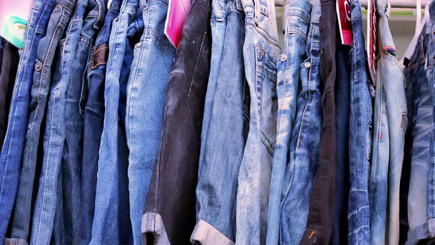 Close up of many blue jeans hanging on a rail. Video macro shift motion