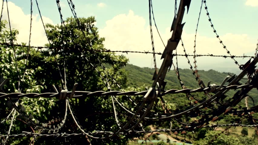 Barbed wire blocking beautiful nature. Pan to show spiraling wire and road.