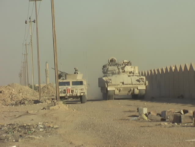 Iraq, Circa, 2005: Bradley Armored Vehicle and Humvee on Patrol in a remote village in Iraq, Circa, 2005