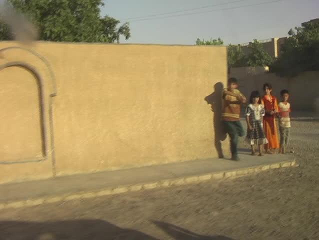 Iraq, Circa 2005: Iraqi children playing on a corner taunt a passing vehicle in Iraq, Circa 2005