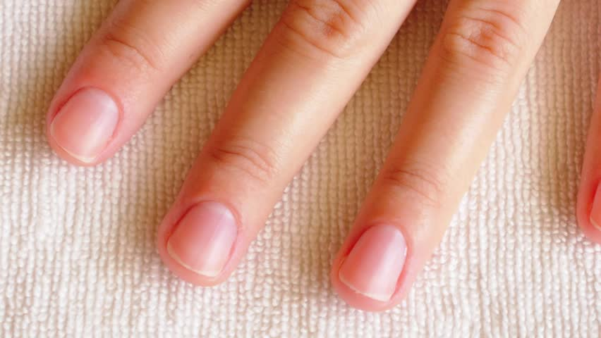 Woman Painting Nails with Orange Color after Manicure. Close up.