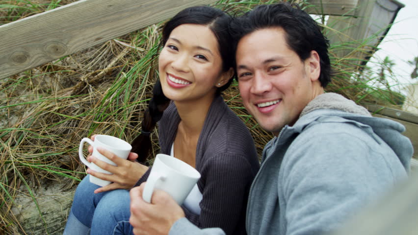 Laughing young Asian Chinese couple close up keeping warm drinking coffee Fall beach vacation enjoying fresh coastal air smiling camera shot on RED EPIC
