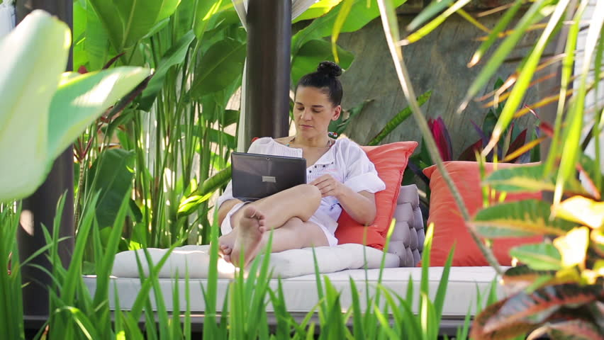 Happy woman finish working on laptop and resting in exotic garden
