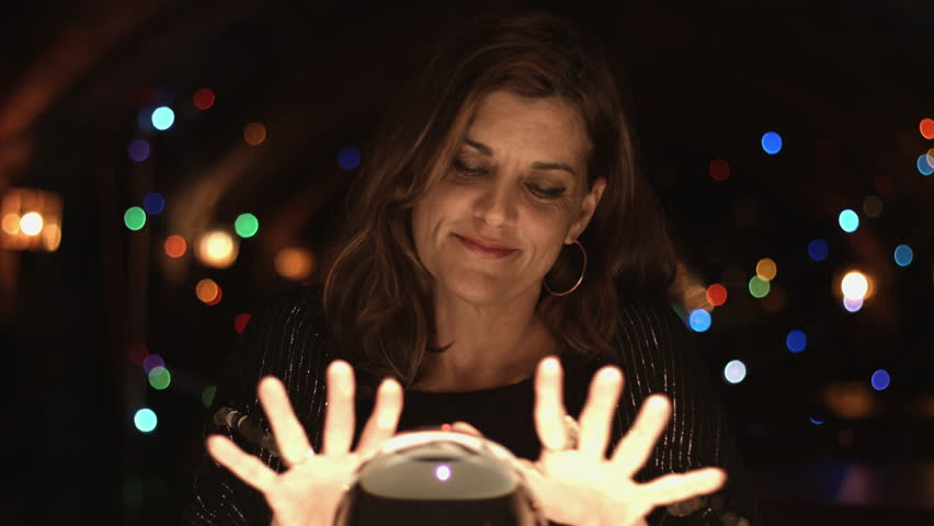Fortune teller beckons people to join her in viewing a crystal ball.  Medium close up.  UHD 4K.
