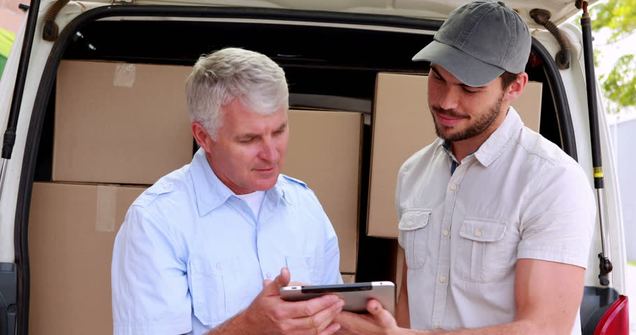 Delivery driver using tablet to take customers signature in a large warehouse - 4K stock footage clip