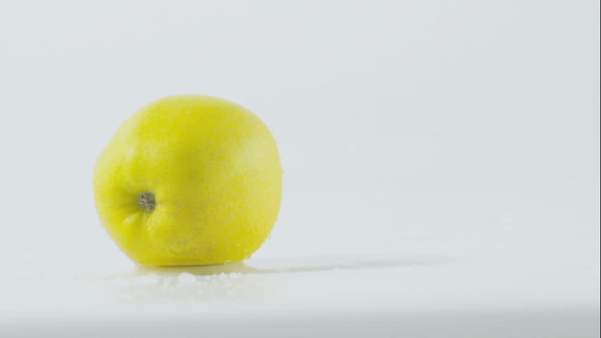 Yellow apple falling on wet surface slow motion