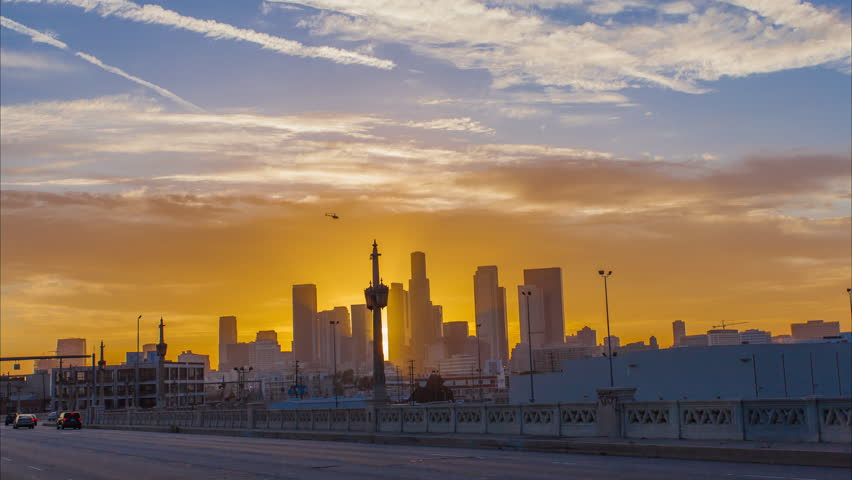 Red sunset over big city. Timelapse in motion (hyperlapse). Transition from day to night. Spectacular cloudy sky. Camera moving by the bridge. Downtown, Los Angeles, California.