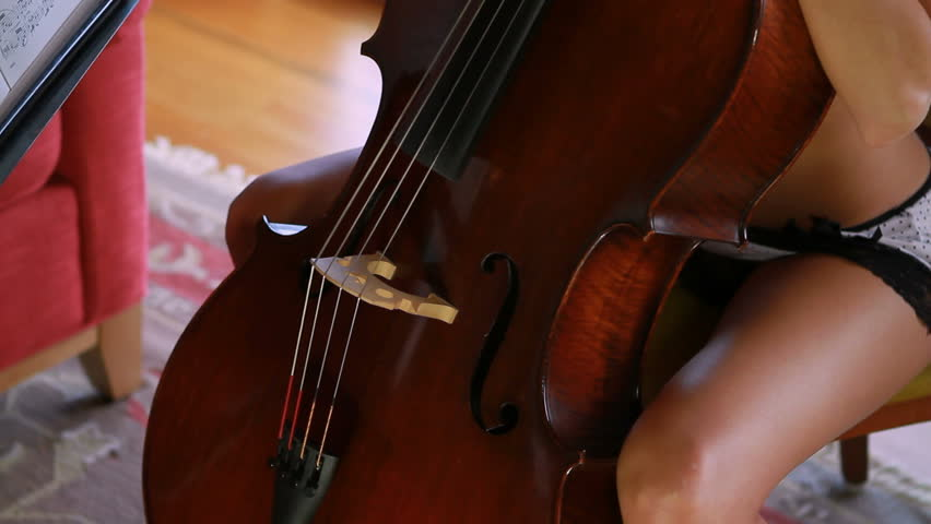 A beautiful cellist studies the music in detail.   - HD stock footage clip