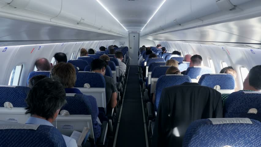 inside airplane. passengers siting in plane. air travel. flight flying. business trip. vacation - 4K stock footage clip