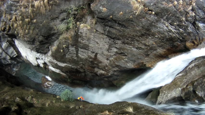 A canyoneer abseils next to a waterfall into a canyon