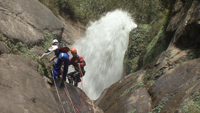 Two canyoneers get ready to abseil down a waterfall
