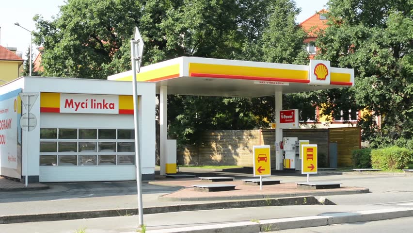 PRAGUE, CZECH REPUBLIC - AUGUST 14, 2014: gas station (oil pump) Shell in the city - with cars and people. Passing cars with forest. Car wash and gas station for trucks.
