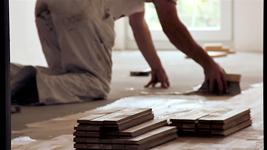 Carpenter worker installing glue for wood parquet board during flooring - HD stock footage clip