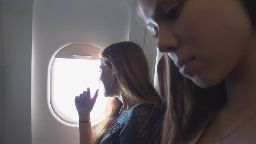 Two girls looks out from airplane window during air travel. Smiling. Happy. Young women travelling by plane together. Tourists. Tourism concept. Slow motion 240 fps. HD 1080. High speed camera shot.