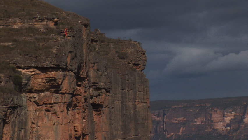 A base jumper jumps off a cliff - HD stock video clip