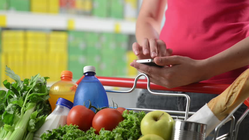 Woman using mobile phone at supermarket hands close-up.