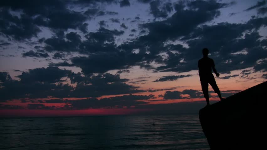 young man stands on rock and throws pebbles into sea under sunset sky  - HD stock video clip