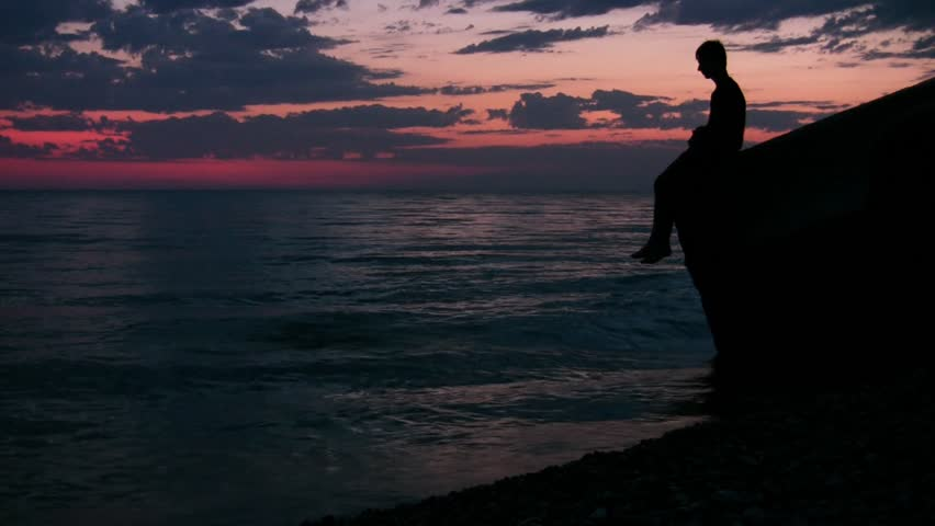 silhouette of teenager sits against sunset sky and throws stones into sea  - HD stock footage clip