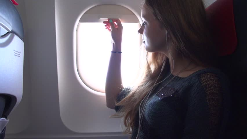 Young women Traveling by Plane together. Girl looks out from Airplane Window during air travel, Listening Music and using ipad. Smiling teen girl in the plane using tablet computer. Slow motion 1080