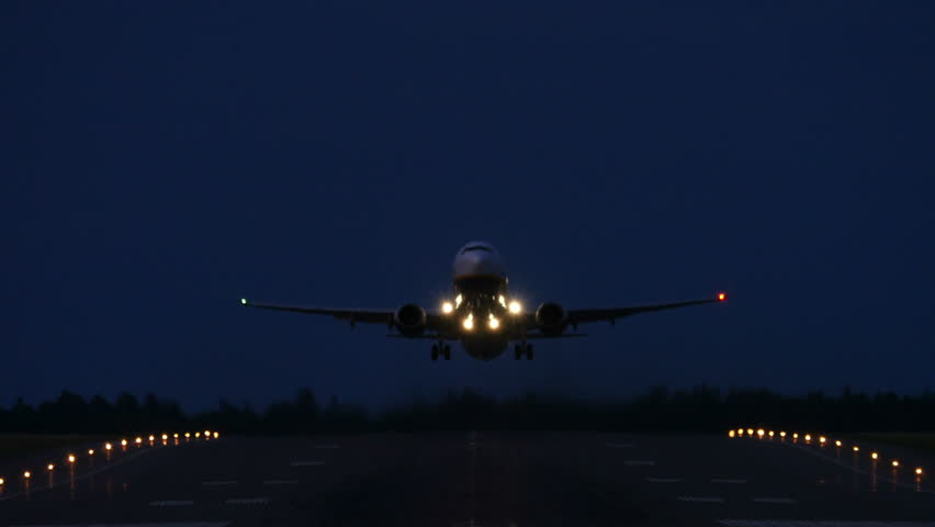 Airliner taking off from an Airport at night, head on, 4k.