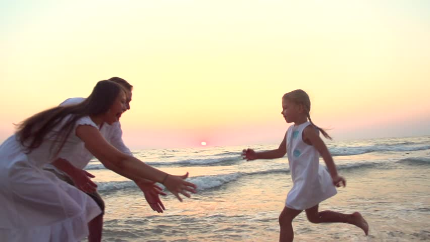 Happy family having fun outdoors. Beautiful a little girl in a white dress running towards parents along coastline. Young happy family walking seashore Slow motion 240 fps HD 1080p. High speed camera - HD stock video clip
