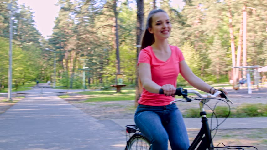 Smiling teenage girl riding bicycle in a park