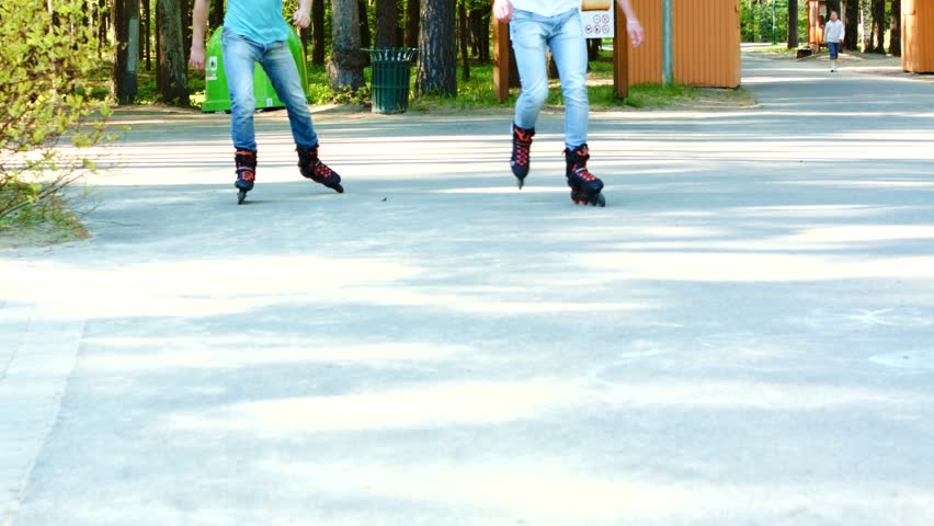 Two young men on rollerblades in a park