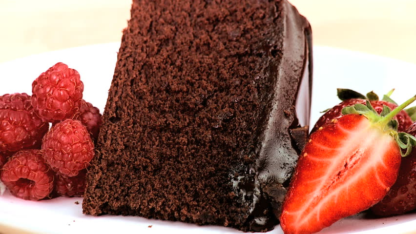 Indulgent chocolate cake & strawberries being covered in sweet sticky sauce on white background - HD stock video clip