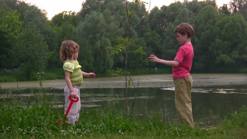 boy with bucket and girl with shovel near young plant against pond