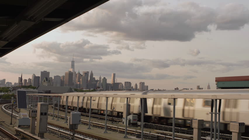 NEW YORK - AUGUST 8, 2014: Manhattan Skyline from Brooklyn subway station with F train at sunset in 4K in New York. Manhattan is the smallest yet most densely populated of the five boroughs of NYC.
