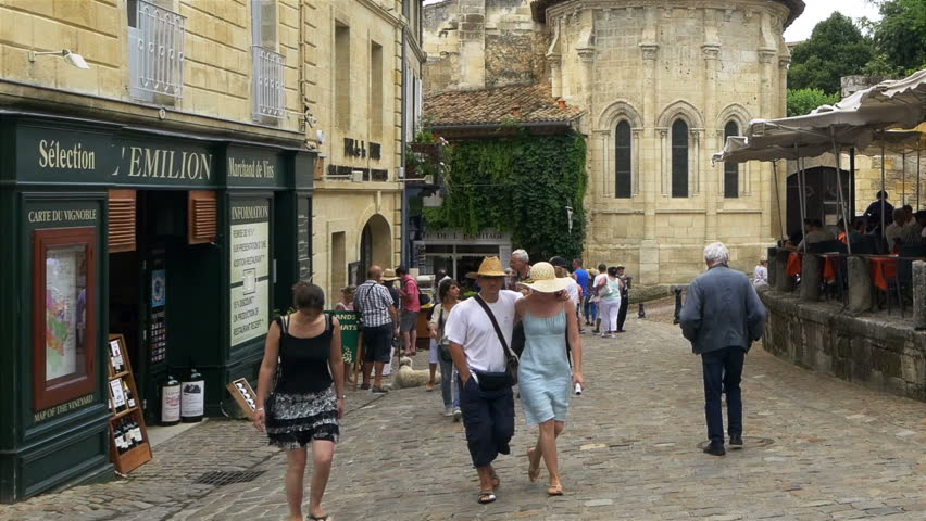 ST. EMILION FRANCE - AUGUST 2014: Tourists in the Place de L'eglise Monolithe in the center of the town. This area is full of restaurants and wine shops such as the one to the left of screen.