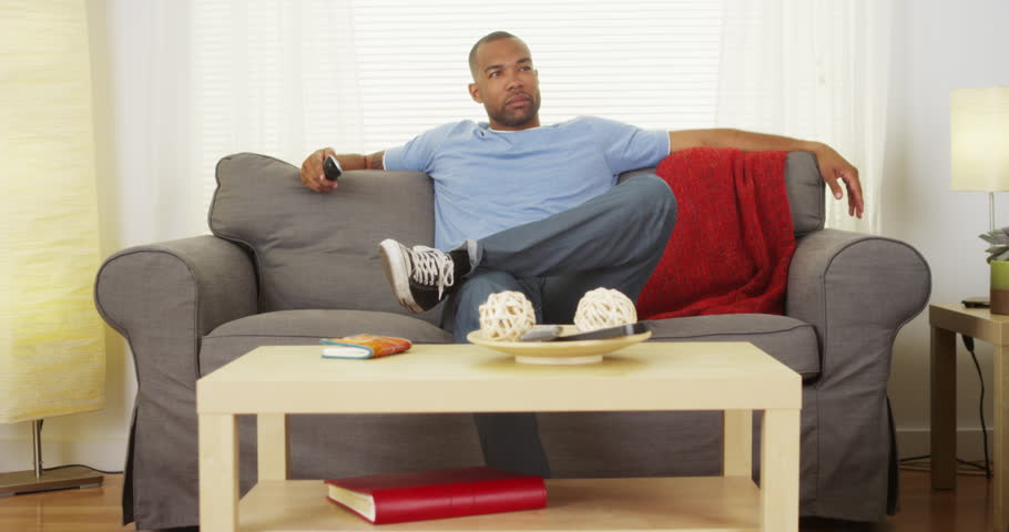 Black man sitting on couch watching tv - 4K stock footage clip