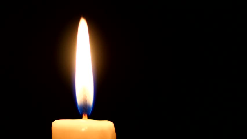 Close-up of a candle flame on a black background. Loop.