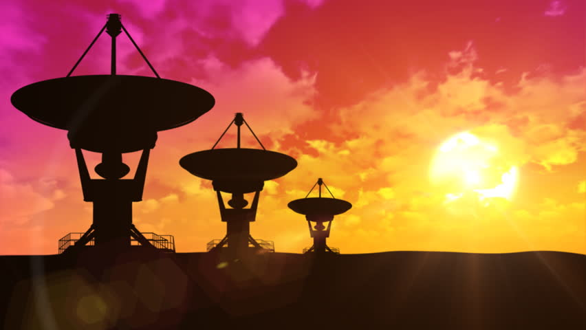 Silhouettes of rotating satellite antennas at sunset with timelapse clouds in background. Seamless loop. - HD stock video clip