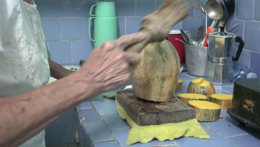 Senior Cuban woman in her kitchen cutting, preparing and cooking a pumpkin