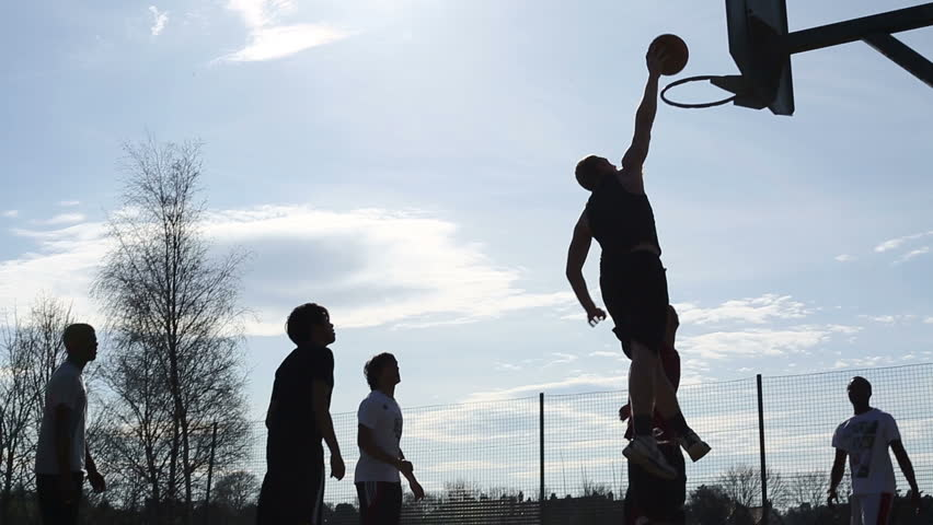 Silhouette game of basketball where one player slam dunks against the defenders - HD stock video clip