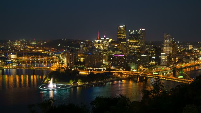 (Time-lapse) Night falls on the downtown area of Pittsburgh, Pennsylvania including the skyline, bridges, and Point State Park at the confluence of the Allegheny and Monongahela Rivers. - 4K stock footage clip