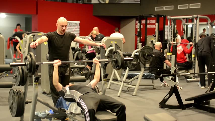 PRAGUE, CZECH REPUBLIC, FITNESS GALAXIE - JANUARY 7, 2014: Man strengthens the pectoral muscles in fitness. Workout bench press and biceps