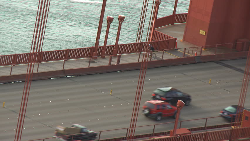 Cyclists and morning traffic moves across San Francisco's Golden Gate Bridge. - HD stock video clip