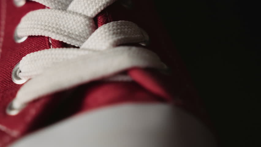 White shoelace on red shoes HD stock footage. A close up dolly shot of white shoelaces on some red shoes set against a black background.