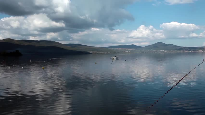Calm waters and beautiful clouds reflected - Bracciano Lake, Lazio, Italy. High resolution video (1920 x 1080).