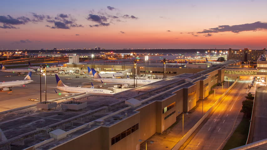 HOUSTON, TX - 2014: George Bush Intercontinental Airport IAH Timelapse with a Medium Pan towards Terminal C at Dusk Sunset in Houston Texas