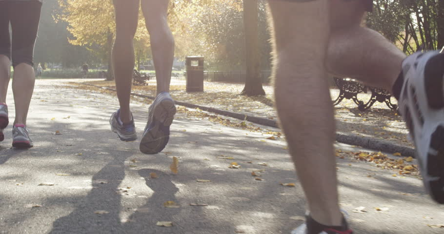 close up feet Group of runners running in park wearing wearable technology connected devices