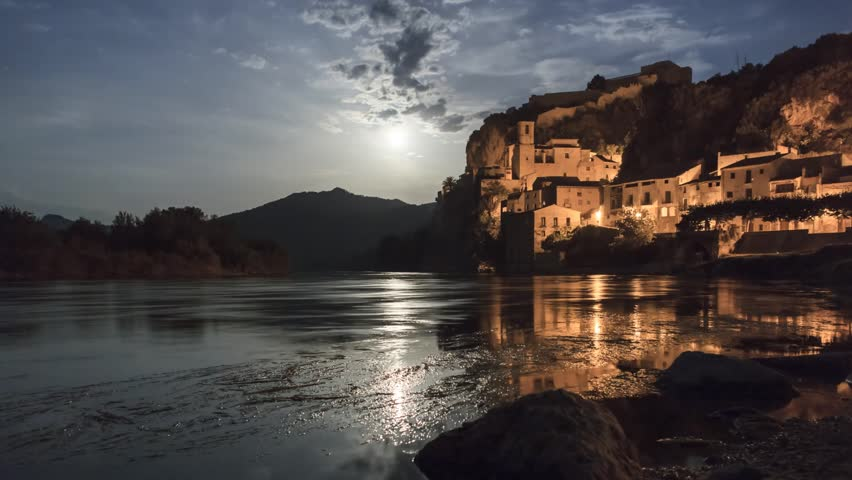 Moon setting over the river Ebro at Castle Miravet, Catalonia, Spain. Timelapse footage.