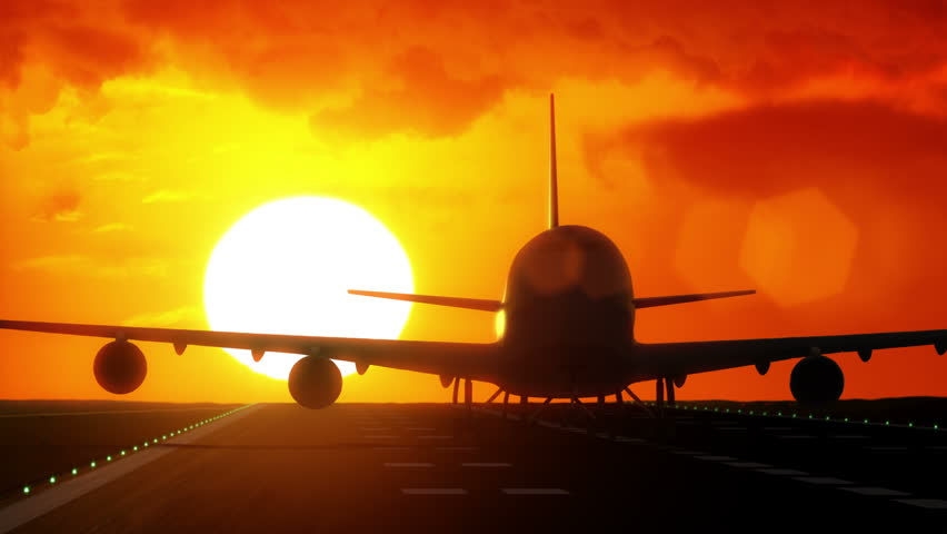 Jet plane departs from airport runway as silhouette in front of large sunset / sunrise 4K UltraHD